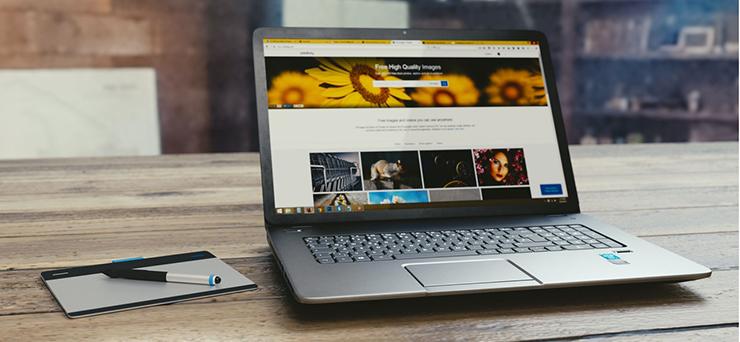 Ein aufgeklappter Laptop steht auf einem massiven Holztisch. Auf seinem Bildschirm ist eine Website zu sehen.